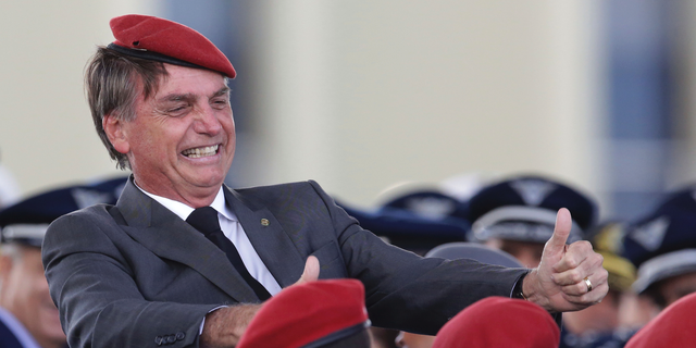 FILE - In this April 19, 2018 file photo, presidential hopeful, conservative Brazilian lawmaker Jair Bolsonaro flashes two thumbs up as he poses for a photo with cadets during a ceremony marking Army Day, in Brasilia, Brazil.  Bolsonaro, the leading candidate in Brazil's presidential race was discharged from the hospital Saturday, Sept. 29, 2018, where he was being treated for a knife wound to his abdomen. (AP Photo/Eraldo Peres, File)