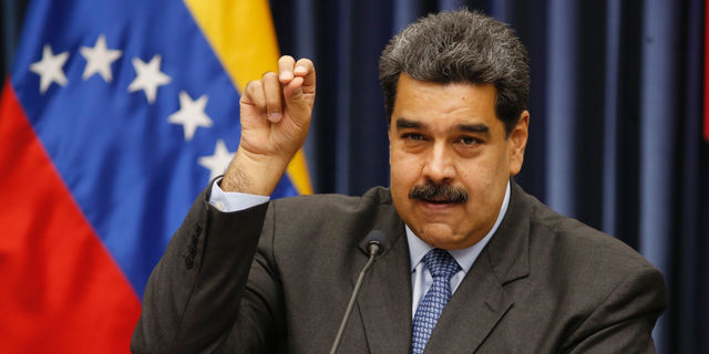 Venezuela's President Nicolas Maduro demonstrates his Salt Bae sprinkling technique during a press conference at the Miraflores Presidential Palace, in Caracas, Venezuela, Tuesday, Sept. 18, 2018. Maduro demonstrated the technique after speaking about the invitation to the famed Nusr-Et steakhouse in Istanbul when he stopped over briefly in Turkey on the way home from a trip to China to raise badly needed investment. Videos of Maduro feasting on a steak is drawing fury from opponents of the embattled socialist leader. (AP Photo/Ariana Cubillos)