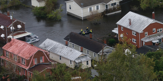 Rescue personnel use a small boat as they go house to house checking for flood victims from Florence in New Bern, NC., Saturday, Sept. 15, 2018. (AP Photo/Steve Helber)
