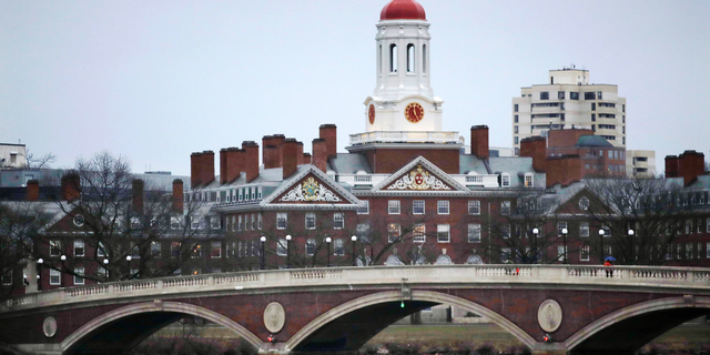 In this March 7, 2017 file photo, rowers paddle along the Charles River past the Harvard College campus in Cambridge, Mass.