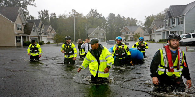 Members of the North Carolina Task Force urban search and rescue team wade through a flooded neighborhood looking for residents who stayed behind as Florence continues to dump heavy rain in Fayetteville, N.C., Sunday, Sept. 16, 2018. (AP Photo/David Goldman)