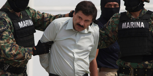 """FILE - In this Feb. 22, 2014, file photo, Joaquin """"El Chapo"""" Guzman is escorted to a helicopter in handcuffs by Mexican Navy marines in Mexico City, Mexico. A . (AP Photo/Eduardo Verdugo, File)"""