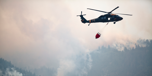 This photo taken Aug. 6, 2018, shows a helicopters returning from performing an air operation on the Coal Hollow Fire near U.S. Highway 6. An Idaho prisoner sent to help fight a wildfire in Utah raped a woman who also was working to support firefighters, prosecutors said Tuesday, Sept. 4, 2018. The woman had rejected several advances from Ruben Hernandez, 27, in the days before the Aug. 29 assault at the base camp, Sanpete County attorney Kevin Daniels said. Hernandez has been charged with felony rape. (Evan Cobb/The Daily Herald via AP)