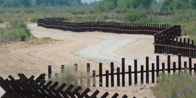 """This June 15, 2017, photo provided by Kenneth Madsen, shows a post-on-rail style of fence along the flood plain of the Colorado River between Arizona and Baja California, which is typical of border wall fences placed in environmentally sensitive areas or in areas prone to flooding. A new photo exhibit by Madsen opening Wednesday, Sept. 19, 2018, at the Ohio State University-Newark campus, """"Up Close with U.S.-Mexico Border Barriers,"""" highlights different types of border wall fencing. (Kenneth Madsen via AP)"""