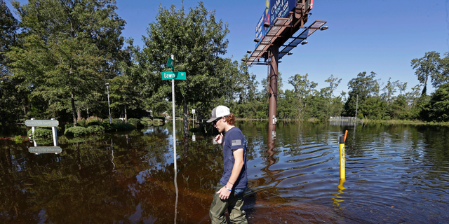 Zachary Conner wades into a flooded neighborhood to check on his girlfriend in Lumberton, N.C., Tuesday, Sept. 18, 2018, following the effects from Hurricane Florence. (AP Photo/Gerry Broome)