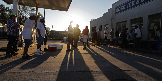FILE - In this Sept. 19, 2018, file photo, people begin to form a line in the morning sun as they wait outside Rose Ice & Coal for it to open days after Hurricane Florence in Wilmington, N.C. Many in Wilmington woke up Wednesday suddenly very tired. The days-long scavenger hunt for gas and ice was over as stores opened and relief agencies were able to roll into the city. (AP Photo/Chuck Burton, File)