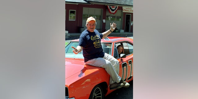 In this Aug. 10, 1999, file photo, 'Cooter,' actor Ben Jones, sits atop one of the 229 hotrods, named The General Lee, used in the show 'Dukes of Hazzard' in front of his store in Sperryville, Va.