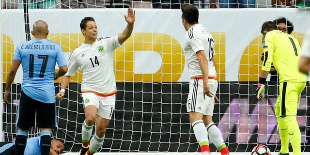 "Mexico forward Javier ""Chicharito"" Hernandez (14) high fives Hector Herrera, right, after Herrera scored a goal during the first half of a Copa America group C soccer match against Uruguay at University of Phoenix Stadium, Sunday, June 5, 2016, in Glendale, Ariz. (AP Photo/Matt York)"