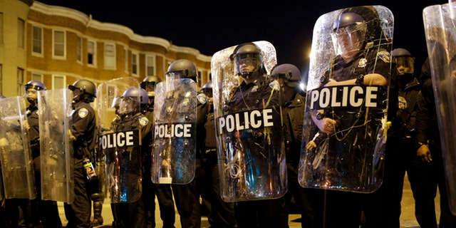 FILE - In this April 28, 2015 file photo, police stand in formation as a curfew approache in Baltimore, a day after unrest that occurred following Freddie Gray's funeral. (AP Photo/Patrick Semansky, File)