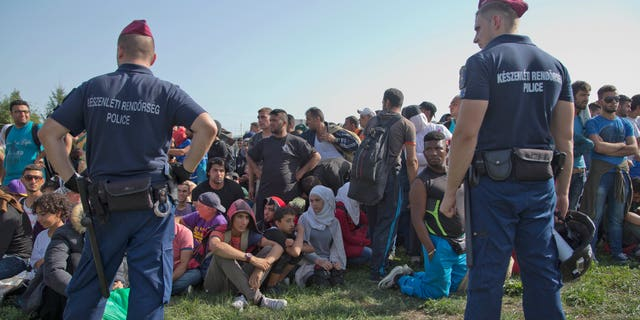 Sept. 18, 2015 - Migrants wait after disembarking from Croatian buses in Baranjsko Petrovo Selo, at the Hungarian border, northeast Croatia. Croatia has sent buses full of migrants to Hungary after the country's prime minister said it could not cope with the influx.
