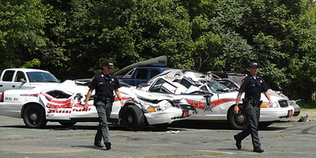 Aug. 2, 2012: Sheriff officers walk past crushed cruisers at the Orleans County Sheriff's Department in Newport, Vt.