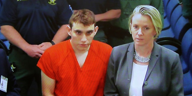 Nikolas Cruz is seen during a hearing flanked by his lawyer Diane Cuddihy.