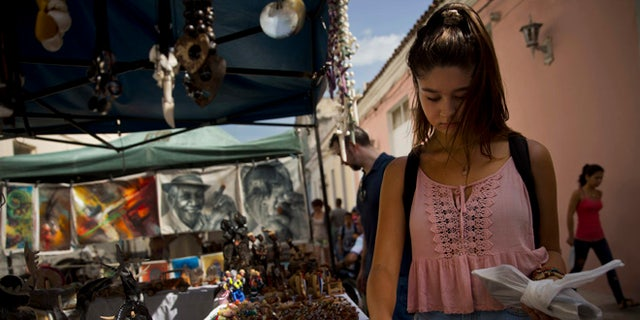 """In this Sept. 1, 2016 photo, tourist Sophia Compton from Chicago looks for souvenirs at a market in Santa Clara, Cuba. """"The best tourist there is, is the American tourist,"""" said 25-year-old Liban Bermudez as he sold Compton a pair of handmade leather sandals from his stand off Santa Clara's main plaza. """"They're the ones that buy the most."""" (AP Photo/Ramon Espinosa)"""