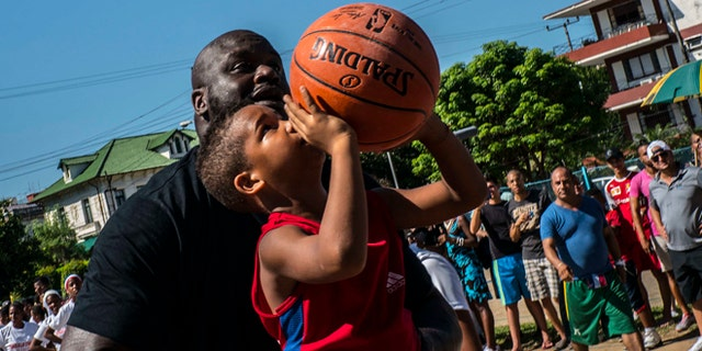 Shaquille O'Neal, plays with a youngster during a clinic with young players in Havana, Sunday, June 26, 2016.