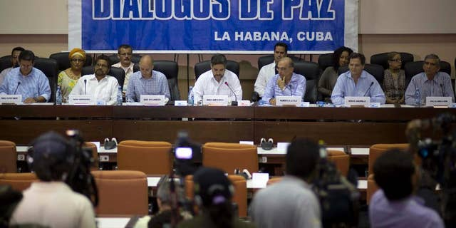 """FILE - In this May 16, 2014 file photo, negotiators from the Revolutionary Armed Forces of Colombia (FARC), left, and Colombia's government, right, give a press conference under a sign that reads in Spanish """"Peace Talks"""" in Havana, Cuba. Colombia's government has rebuffed a unilateral truce declared on Wednesday, Dec. 18, 2014 by the country's largest rebel group, saying conditions demanded by the guerrillas' are unacceptable until a peace deal is reached. Sitting at the table, from left, are chief of the western bloc of the FARC Pablo Catatumbo, FARC chief negotiator Ivan Marquez, Norwegian guarantor Dag Nylander, Cuban guarantor Rodolfo Benitez Verson, head of Colombia's government team Humberto de la Calle, government negotiator Sergio Jaramillo, and government negotiator Gen. Jorge Mora. (AP Photo/Ramon Espinosa, File)"""