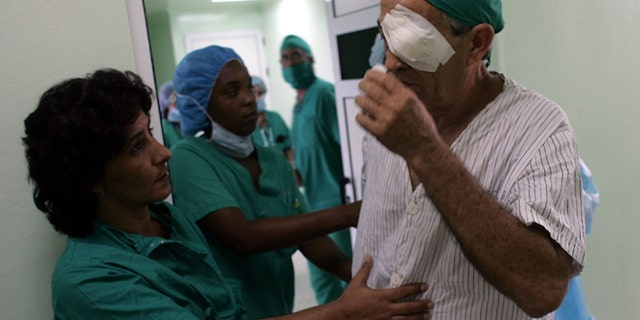 """HAVANA - SEPTEMBER 12:  Doctors help a patient after he had eye surgery performed by doctors participating in """"Operacion Milagro"""" (Operation Miracle) September 12, 2006 at Pando Ferrer hospital in Havana, Cuba. The program is a joint health care program setup between Cuba and Venezuela which offers free eye care in Cuban hospitals for people living in Latin America and the Caribbean.  (Photo by Joe Raedle/Getty Images)"""