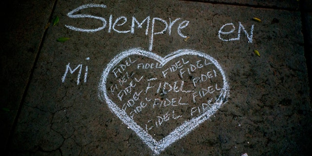 """A heart and the text that reads in Spanish """"Always in my heart Fidel"""" are outlined in chalk on a sidewalk, during a vigil at the university where the late Cuban leader Fidel Castro studied law as a young man in Havana, Cuba, Saturday, Nov. 26, 2016. Castro, who led a rebel army to improbable victory in Cuba, embraced Soviet-style communism and defied the power of U.S. presidents during his half century rule, died at age 90. (AP Photo/Ramon Espinosa)"""