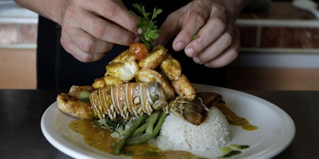 """In this photo taken Friday, April 29, 2011, chef Diomer Matos prepares """"Esclava de Langosta,"""" a lobster dish, at La Moneda Cubana, a private restaurant, in Old Havana, Cuba. A restaurant boom is sweeping Havana under new rules that make it easier to run """"paladars,"""" with a wave of new private eateries opening since January 2011. (AP Photo/Franklin Reyes)"""