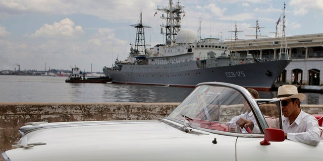 An American classic car passes in front of the Russian warship The Viktor Leonov CCB-175 docked in Havana's harbor in Havana, Cuba, Thursday, Feb. 27, 2014. A Russian warship, one of the fleets Vishnya-class ships which are generally used for intelligence gathering was docked in the Havana harbor on Thursday, a day after the country's defense minister announced plans to expand Russia's worldwide military presence. (AP Photo/Franklin Reyes)