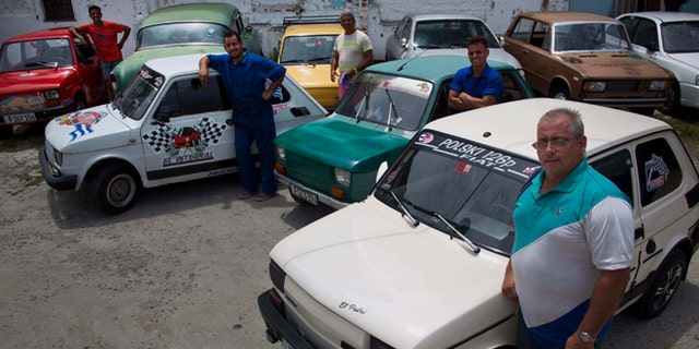 Fiat Polski 126p, owners Raul Seoane, left,  Ramses Fernandez, second left, Evilio Aguilar, center, Rigoberto Mesa, second right, and Pedro Fernandez, proudly pose with their cars in Havana, Cuba, Tuesday, August 10, 2016. With around just 24 horsepower, depending on exactly how each one has been altered, the half-ton Polski offers families a shot at independent mobility for a few thousand dollars, a sum within reach of those able to save from private jobs or family sending money from overseas. (AP Photo/Ramon Espinosa)