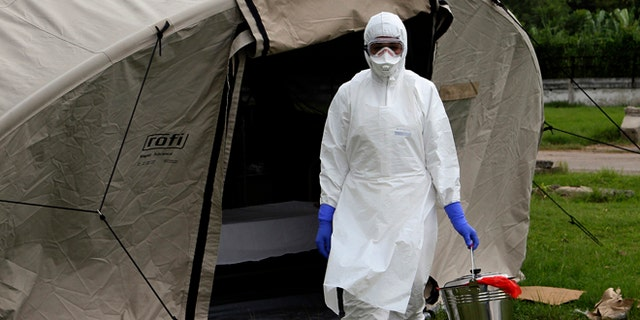 In this Sept. 24, 2014 photo, nurse Dalila Martinez, trainer of the Cuban medical team to travel to Sierra Leone, practices proper disposal at a training camp, in Havana, Cuba. Cuba's health ministry is sending more than 160 health workers to help stop the raging Ebola outbreak in Sierra Leone in early October. They will stay for six months. (AP Photo/Ladyrene Perez, Cubadebate)