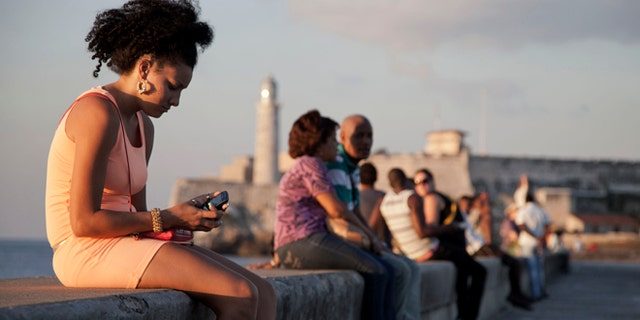 """In this March 11, 2014 photo, a woman uses her cellphone as she sits on the Malecon in Havana, Cuba. The U.S. Agency for International Development masterminded the creation of a """"Cuban Twitter,"""" a communications network designed to undermine the communist government in Cuba, built with secret shell companies and financed through foreign banks, The Associated Press has learned. The project, which lasted more than two years and drew tens of thousands of subscribers, sought to evade Cubas stranglehold on the Internet with a primitive social media platform. (AP Photo/Franklin Reyes)"""