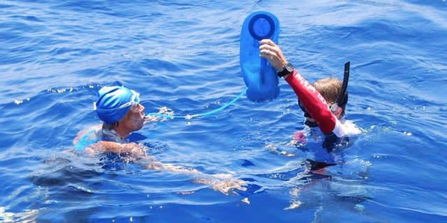 Aug. 20, 2012: In this photo provided by Diana Nyad via the Florida Keys News Bureau, endurance swimmer Diana Nyad is hydrated by a crew member in the Florida Straits between Cuba and the Florida Keys Monday.
