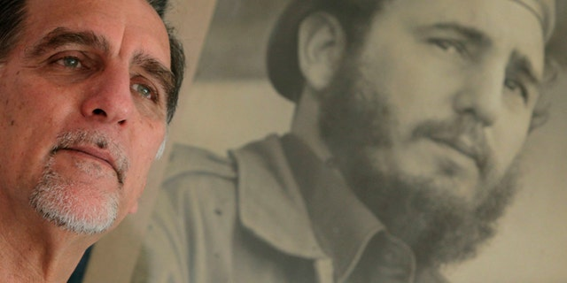 """In this Feb. 17, 2014 photo, Rene Gonzalez, the Cuban Five,"""" poses for a portrait under a framed picture of Fidel Castro in Havana, Cuba.  Gonzalez was an unknown young pilot in 1990 when he pretended to steal a crop duster in Cuba and flew to Florida, using cover as a Cuban defector to spy on targets in the United States. The Cuba Five refers to intelligence agents in the employ of Fidel Castro's Cuba, they were arrested in the United States in 1998 and given terms ranging from 15 years to consecutive life sentences on charges including conspiracy and failure to register as foreign agents.  (AP Photo/Franklin Reyes)"""