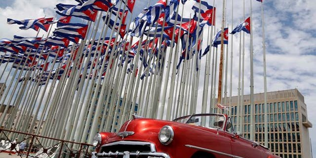 FILE - In this July 26, 2015, file photo, a classic American convertible car passes beside the United States embassy as Cuban flags fly beside in Havana, Cuba. The U.S. doesn't plan to invite Cuban dissidents to Secretary of State John Kerry's historic flag-raising at the American Embassy in Havana on Aug. 14, illustrating a shift in U.S. policy from the island's opposition to its government.  (AP Photo/Desmond Boylan, File)
