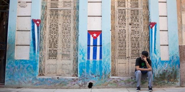 File photo - A man sits on the sidewalk next to Cuban National flags painted on the walls in downtown Havana, Jan. 22, 2015.