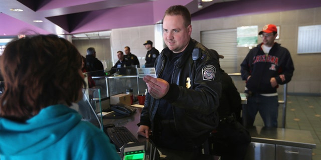 NOGALES, AZ - FEBRUARY 26:  Officer Joe Sokolowski from the Office of Field Operations (OFO) checks identifications at a port of entry from Mexico into the United States on February 26, 2013 in Nogales, Arizona. Some 15,000 people cross between Mexico and the U.S. each day in Nogales, Arizona's busiest border crossing. (Photo by John Moore/Getty Images)