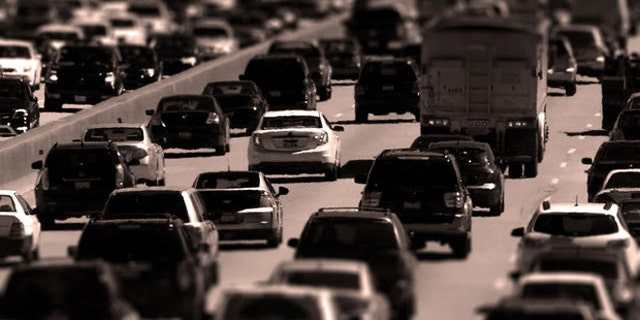 Traffic begins to thicken as motorists getting an early jump to Memorial Day destinations in Indiana and Michigan travel an interstate freeway through Chicago Friday, May 24, 2013. (AP Photo/Charles Rex Arbogast)