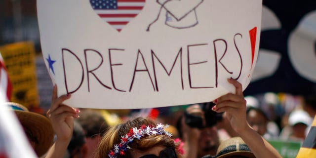 FILE: May 1, 2013: A Dream Act supporter carries a sign during the International Workers Day and Immigration Reform March in Los Angeles, Calif.