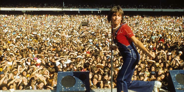 """A young David Cassidy performs at Melbourne Cricket Grounds in Australia in 1974 in an archival photo which airs as part of A&E's Biography Presents: """"David Cassidy: The Last Session"""" premiering Monday, June 11 at 9PM ET/PT."""