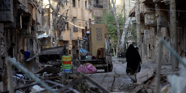 A family moves remnants of their house after it was damaged due to shelling in Deir al zor, Syria October 5, 2013. Now, at least 20 people are suspected of having contracted polio in this war-torn region of the country. (REUTERS/Khalil Ashawi)