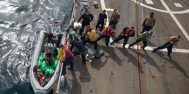 U.S. Navy Sailors aboard the guided-missile destroyer USS Jason Dunham heave a line to load the seized weapons.