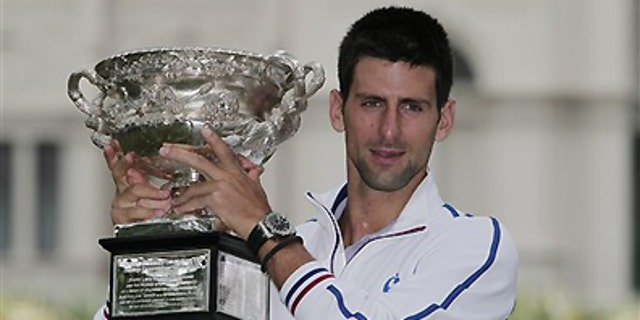 Jan. 30, 2012: Australian Open men's singles champion Serbia's Novak Djokovic poses with his trophy at a park in central Melbourne, Australia. Djokovic defeated Spain's Rafael Nadal in five hours and 53 minutes to win a third Australian Open title earlier in the day.