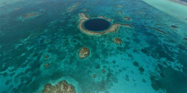This undated image provided by the Belize Tourist Board shows an aerial view of the Great Blue Hole, a popular diving site that's part of Belize's barrier reef.