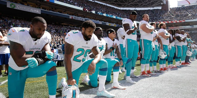 Dolphins players Jelani Jenkins, Arian Foster, Michael Thomas, and Kenny Stills kneeling during the national anthem on Sept. 11, 2016, in Seattle.