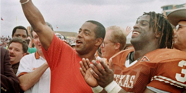 FILE: University of Texas Longhorns Ricky Williams, right, laughs as former Dallas Cowboys star Tony Dorsett signals 'Hook 'em horn' after Williams surpassed Dorsett's NCAA rushing record.