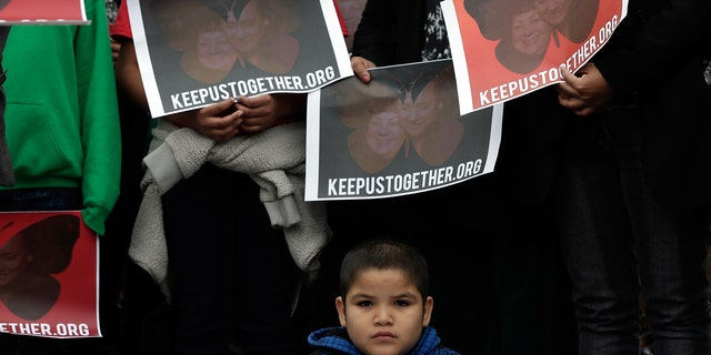 A child listens at a press conference held by the Dream Action Coalition on immigration reform on December 4, 2013 in Washington, DC. (Photo by Win McNamee/Getty Images)