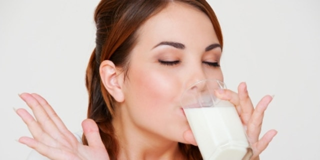 happy young woman drinking milk over grey background