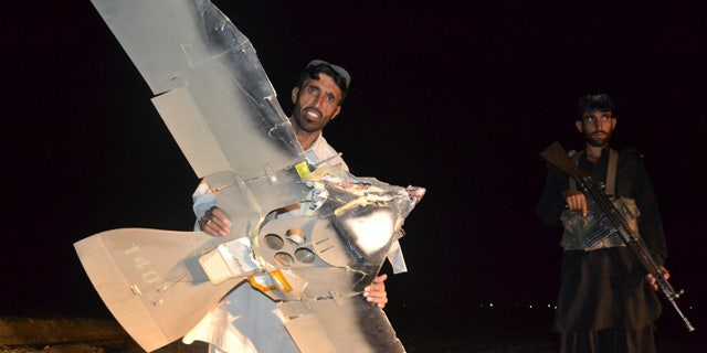 Aug. 25: A Pakistani villager holds a wreckage of a suspected surveillance drone that crashed in Pakistani border town of Chaman along the Afghanistan border.