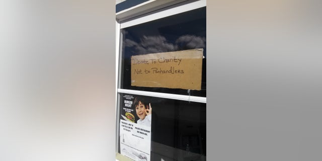 A hand-scrawled sign in Durango, Colorado asking people to donate to homeless groups rather than to panhandlers directly.