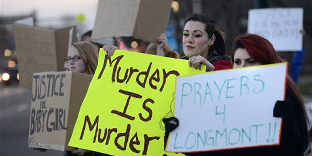 Renee Jacoby, at center, holds a sign with others during a protest against Dynel Lane on Thursday, March 19, 2015, in Longmont, Colo. Lane is accused of stabbing a pregnant woman in the stomach and removing her baby, while the expectant mother visited her home to buy baby clothes advertised on Craigslist authorities said. The baby did not survive. (AP Photo/The Daily Camera, Jeremy Papasso) NO SALES