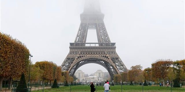 Fog and smog swallow up the top of the Eiffel Tower in Paris Monday, Nov. 2, 2015. Paris authorities have put in place measures to limit traffic after high levels of pollution in the French capital. (AP Photo/Jacques Brinon)