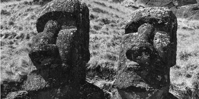 Circa 1955: Two ancient statues of uncertain origin on Easter Island, in the South Pacific Ocean.