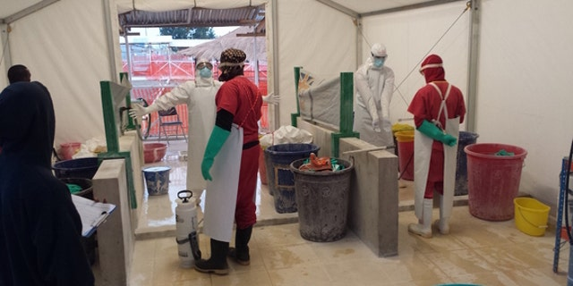 Health care workers prepare to treat patients with Ebola virus at a treatment center in West Africa.
