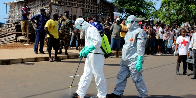 Health workers spray themselves with chlorine disinfectants after removing the body a woman who died of Ebola virus in the Aberdeen district of Freetown, Sierra Leone.