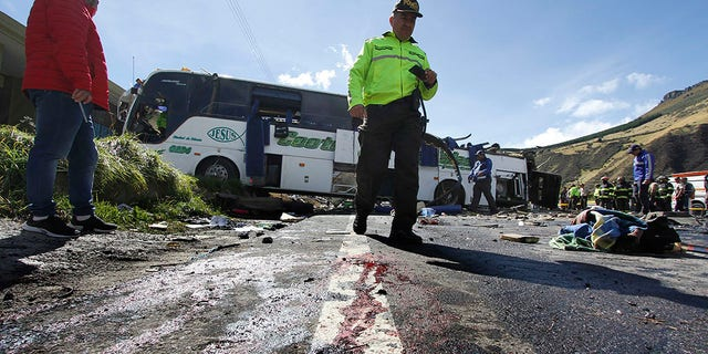 A police officer walks past a Colombian-registered bus traveling to Quito that crashed in Pifo, Ecuador, Tuesday, Aug. 14, 2018. At least 24 people were killed and another 19 injured when a bus careened into another vehicle at high speed and overturned along the Pifo-Papallacta highway, near Ecuador's capital, local officials reported.